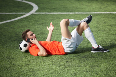Footballer Lying on Pitch on Talking on Phone