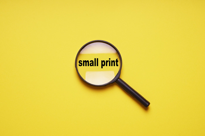 Small Print Highlighted with Magnifying Glass Against a Yellow Background
