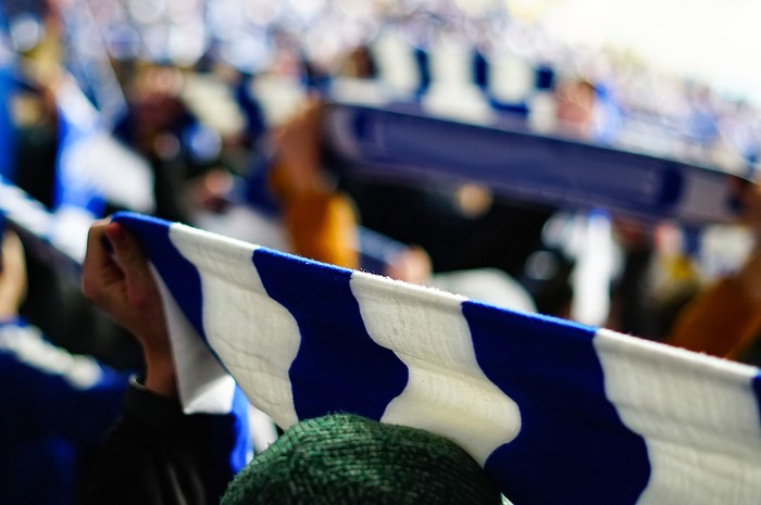 Football Fan Holding Up Blue and White Scarf