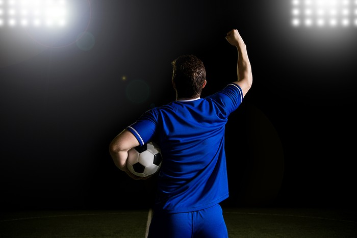 Footballer Celebrating Holding Ball