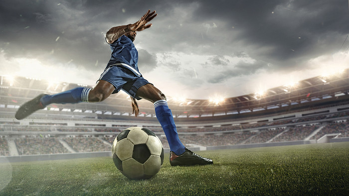 Footballer in Blue Kicking Ball