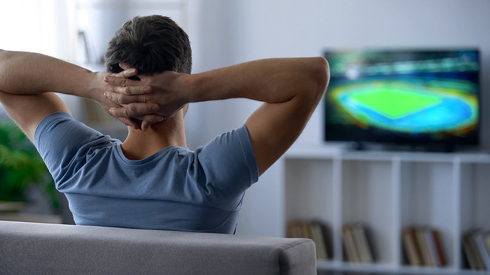 Man Watching Football with Hands Behind Head