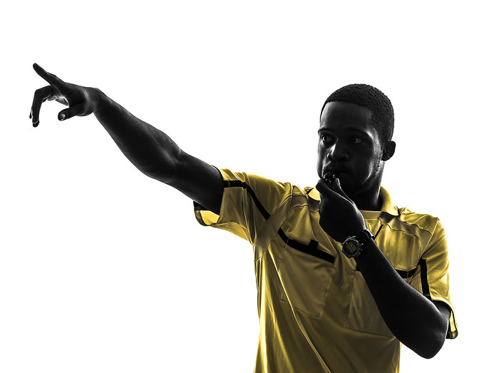 Football Referee Blowing Whistle and Pointing