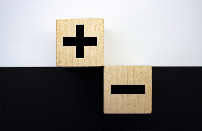 Plus and Minus Wooden Blocks on Black and White Background