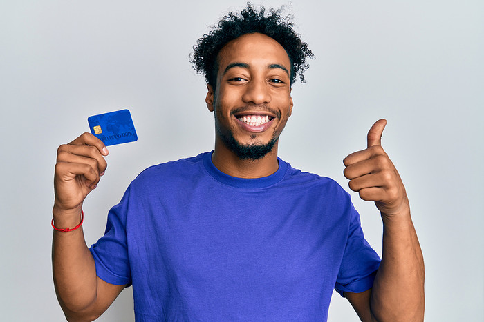 Smiling Man Holding Bank Card With Thumbs Up