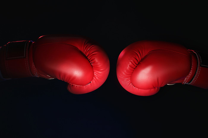 Two Red Boxing Gloves Against Black Background
