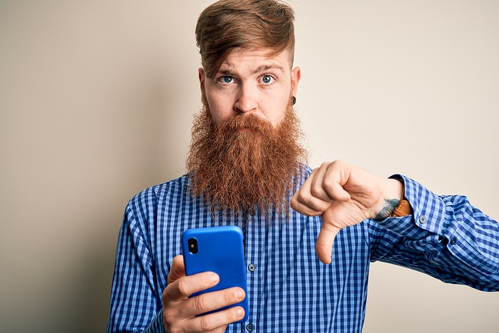 Bearded Man with Smartphone Thumbs Down