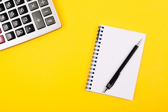 Notepad and Calculator Against Yellow Background