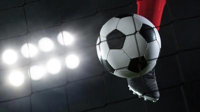 Footballer Scoring Against Floodlight